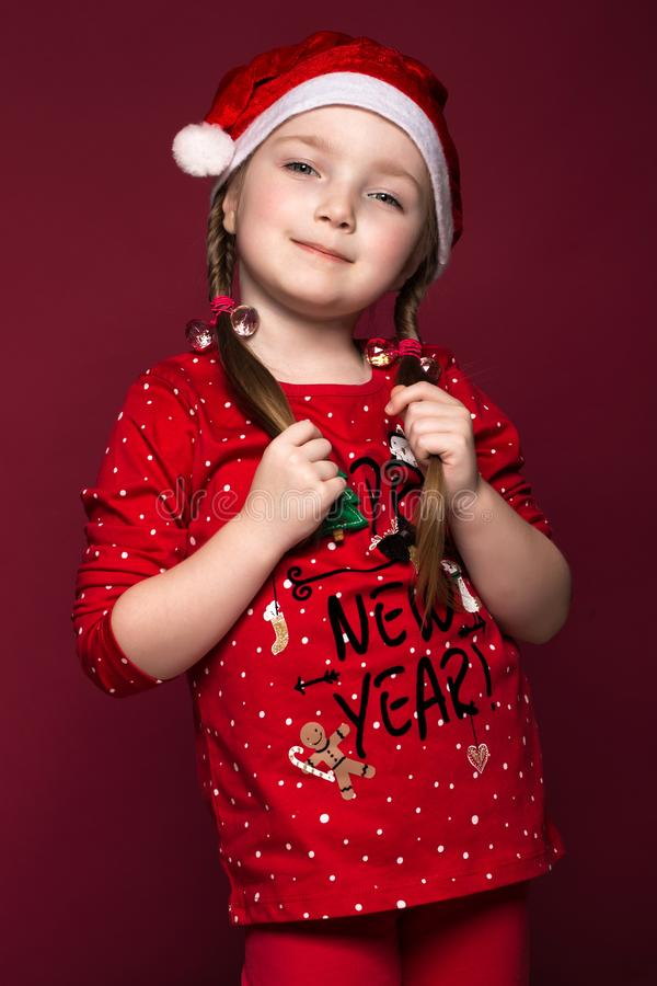 Funny little girl in the New Year`s image, showing different emotions. Photo taken in studio stock photos