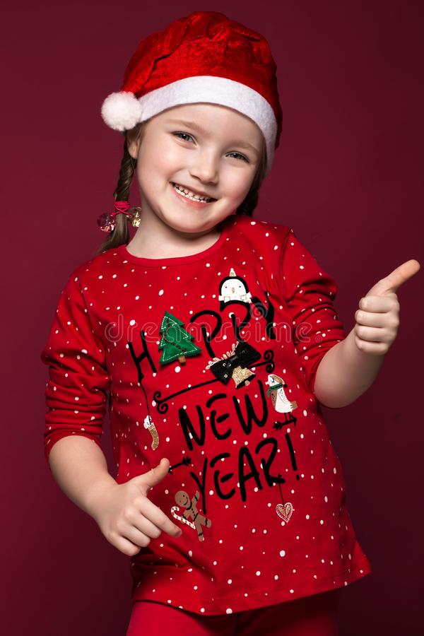 Funny little girl in the New Year`s image, showing different emotions. Photo taken in studio stock photo