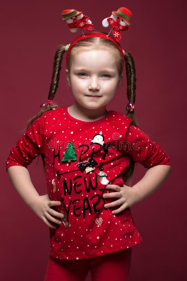 Funny little girl in the New Year`s image, showing different emotions. Photo taken in studio royalty free stock image