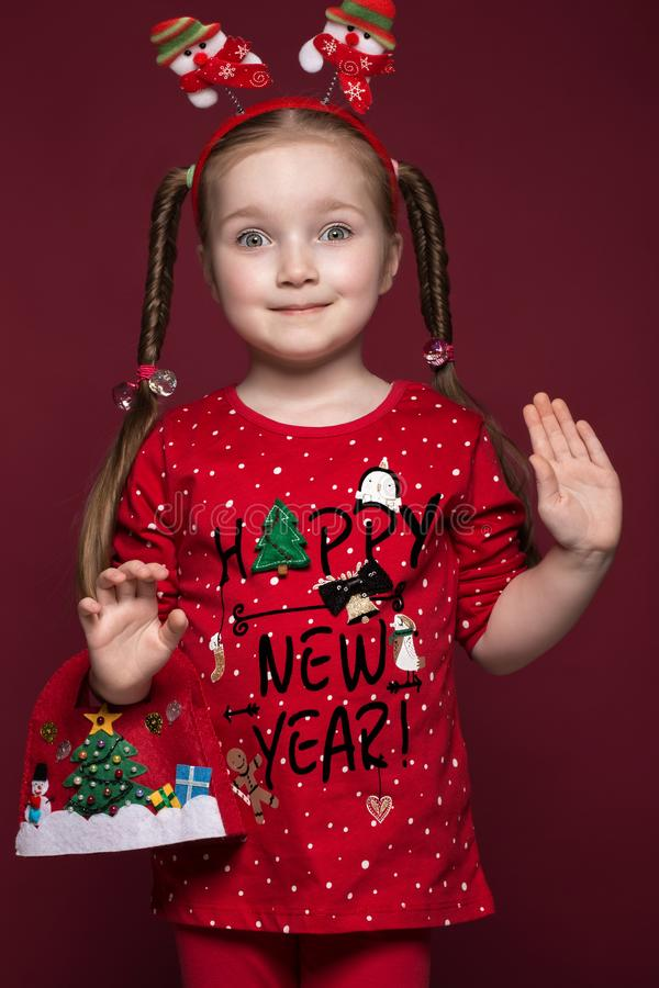 Funny little girl in the New Year`s image, showing different emotions. Photo taken in studio royalty free stock photo