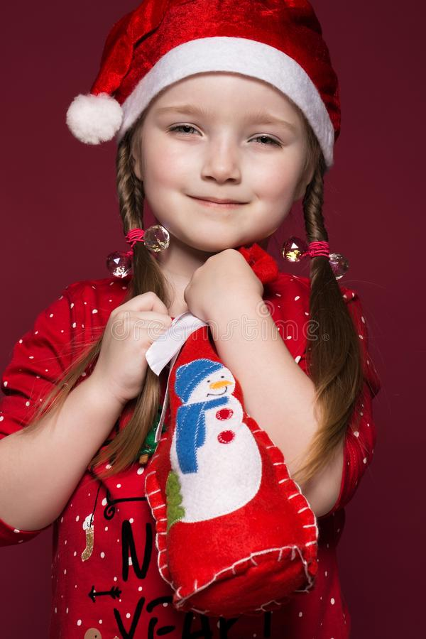 Funny little girl in the New Year`s image, showing different emotions. Photo taken in studio stock images