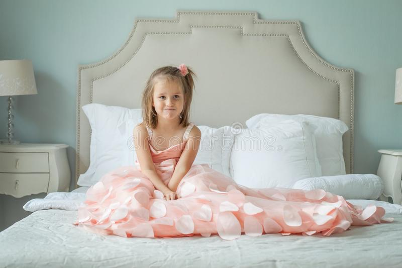 Funny little girl in pink dress sitting on bed stock photo