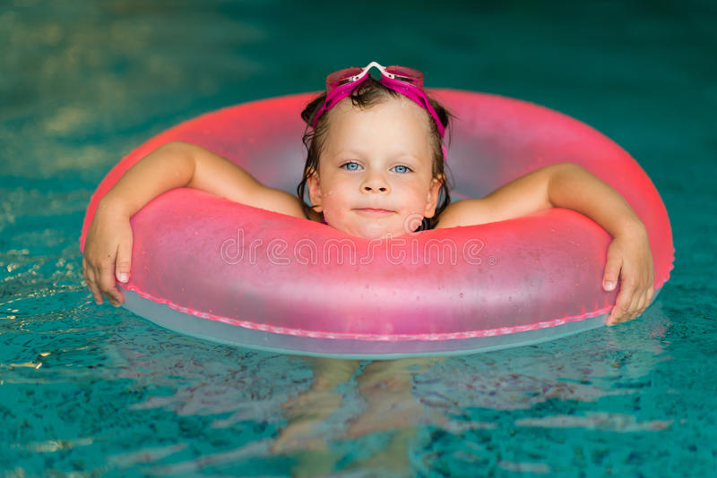 Funny little girl in pink goggles in the swimming pool royalty free stock photography