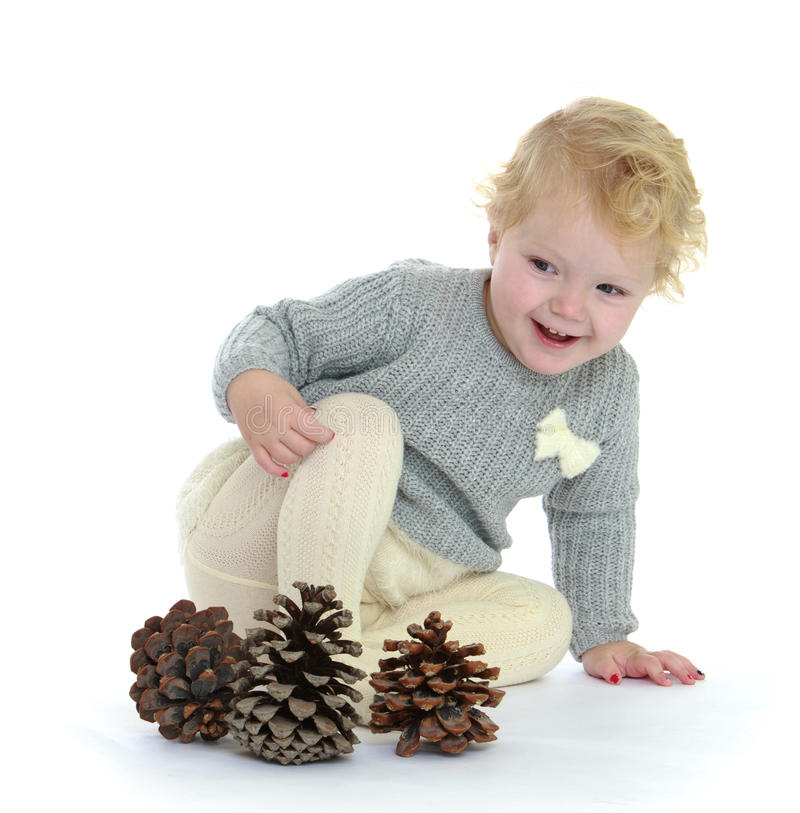 Funny little girl playing with cones sitting on stock photos