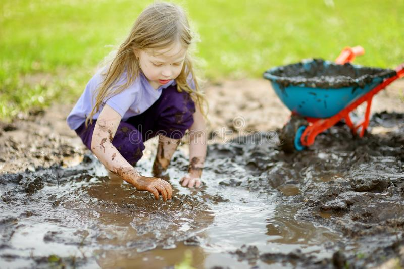 Funny little girl playing in a large wet mud puddle on sunny summer day. Child getting dirty while digging in muddy soil. royalty free stock image