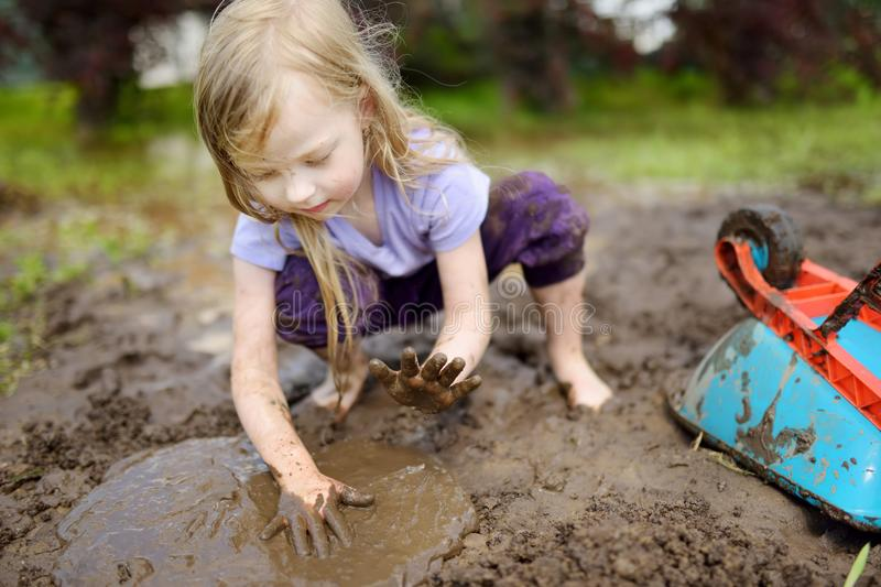 Funny little girl playing in a large wet mud puddle on sunny summer day. Child getting dirty while digging in muddy soil. Messy games outdoors royalty free stock photo