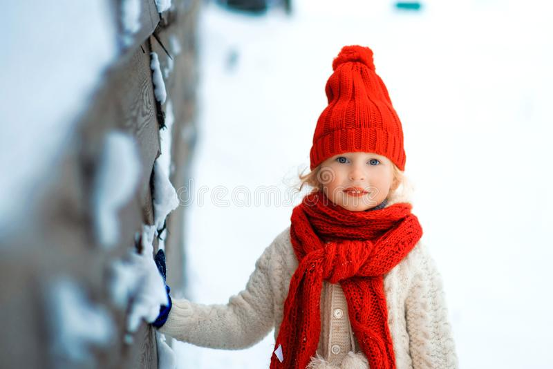 Funny little girl in a red knitted hat and scarf and white pullover playing outside in winter time. Kids play outdoors in winter. stock photography