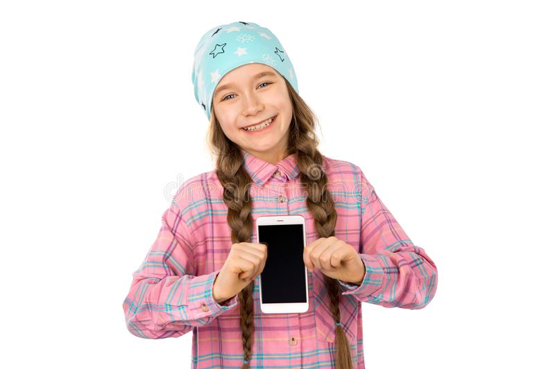 Funny little girl showing smart phone with blank screen on white background. Playing Games and watch video. stock photos