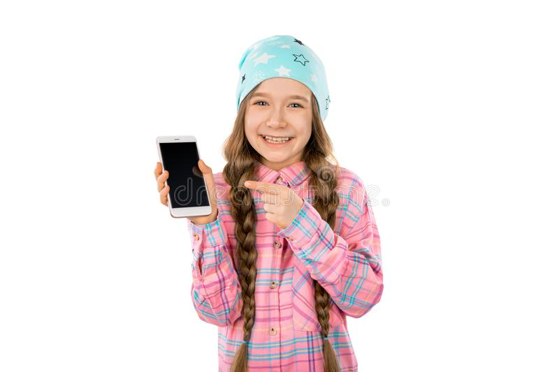 Funny little girl showing smart phone with blank screen on white background. Playing Games and watch video. royalty free stock photography