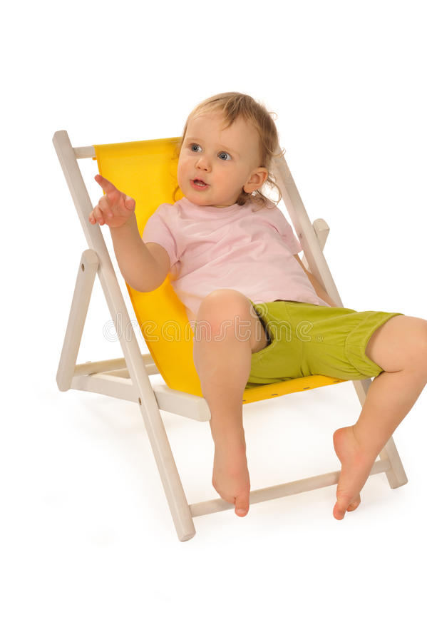 Funny Little Girl In Studio On Yellow Deckchair Royalty Free Stock Images