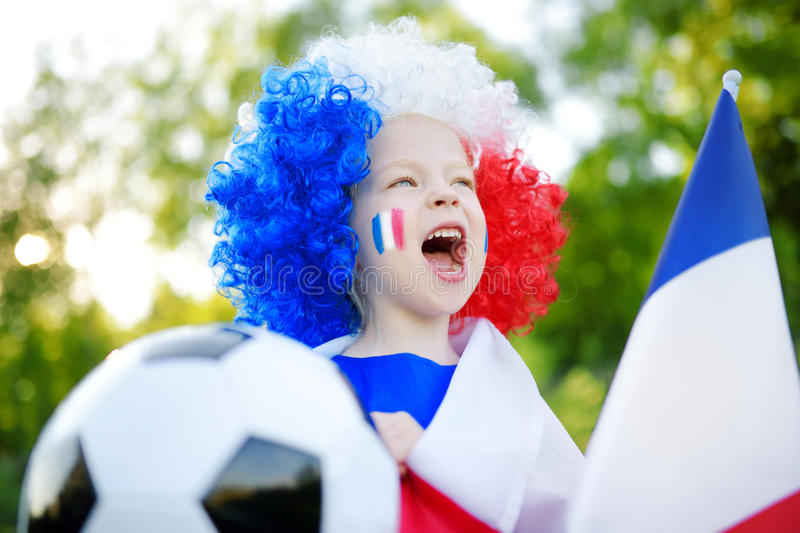 Funny little girl supporting and cheering her national football team. During soccer championship royalty free stock image