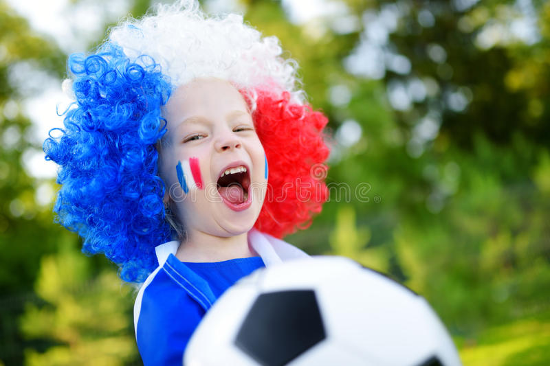 Funny little girl supporting and cheering her national football team. During soccer championship stock image
