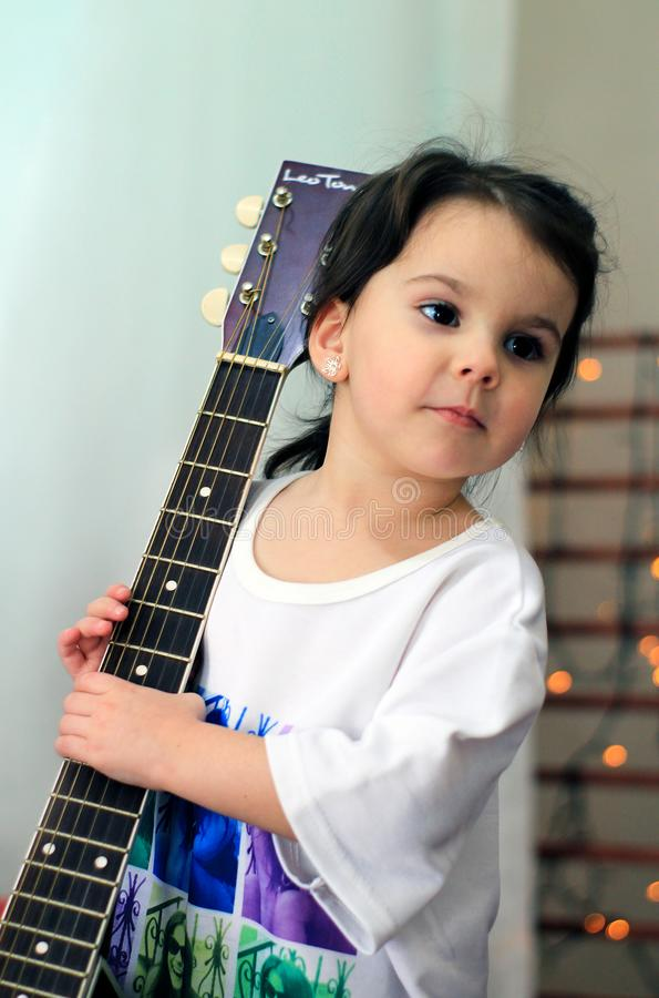 funny little girl in t-shirt holding a guitar royalty free stock photo