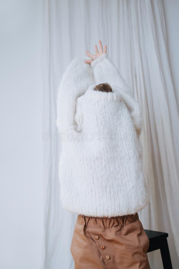 Funny little girl trying to break her head and hands free from inside of sweater royalty free stock photography
