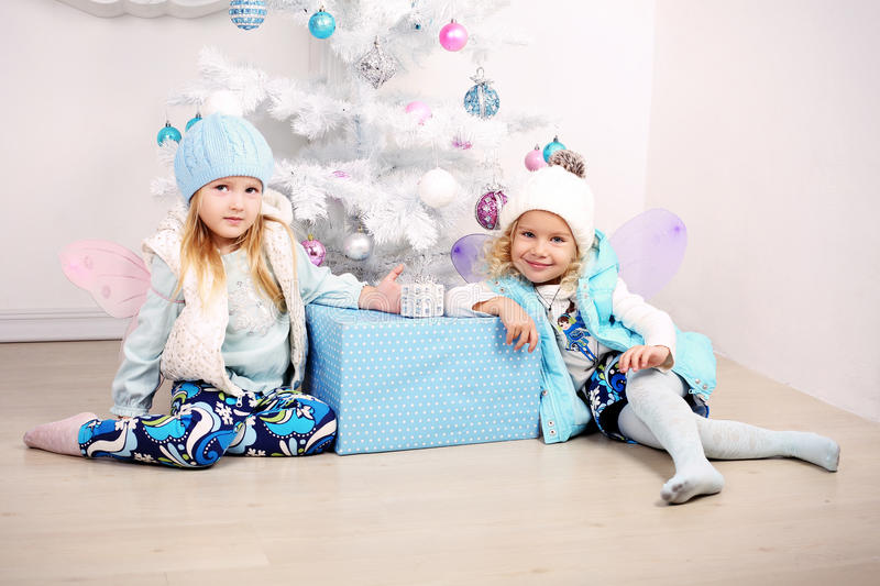 Funny little girls posing beside a decorated Christmas tree stock image