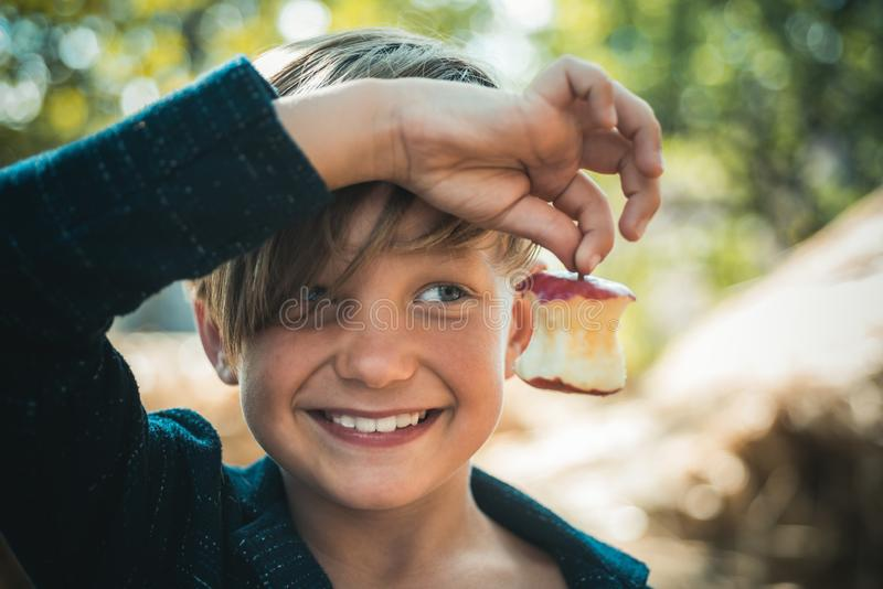Funny little happy boy eating on a farm. Child enjoying autumn season and laughing. Happy childhood, lifestyle concept stock photos