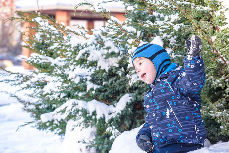 Funny little kid boy in colorful clothes playing outdoors during snowfall. Active leisure with children in winter on cold snowy da. Ys. Happy child having fun stock images
