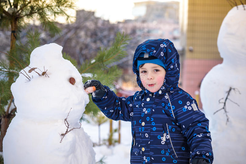 Funny little kid boy making a snowman and eating carrot, playing having fun with snow, outdoors on cold day. Active leisure chil. Funny little kid boy making a stock image