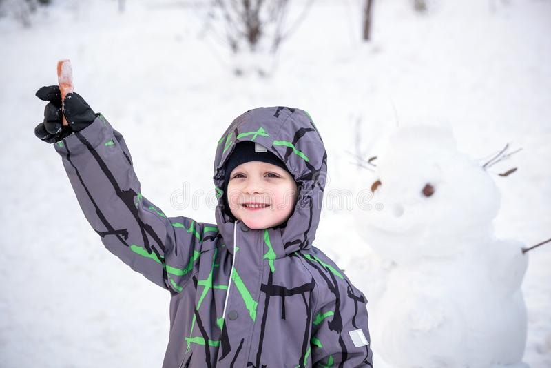 Funny little kid boy making a snowman and eating carrot, playing having fun with snow, outdoors on cold day. Active leisure childr royalty free stock images