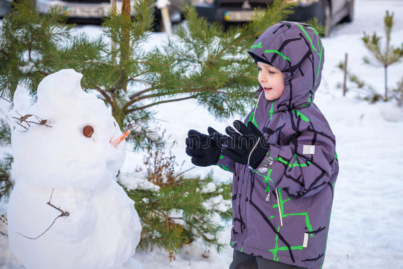 Funny little kid boy making a snowman and eating carrot, playing having fun with snow, outdoors on cold day. Active leisure childr. Funny little kid boy making a stock images
