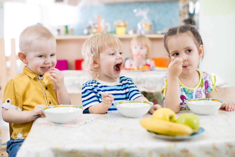Funny little kid with open mouth eating in kindergarten group stock images