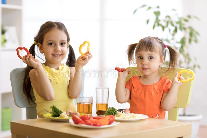Funny little kids playing and eating in kindergarten royalty free stock photography