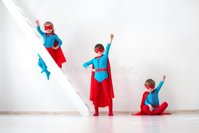 Funny little Kids power super hero. Superhero concept. Kids characters in costumes superheroes posing. Idea stock photo