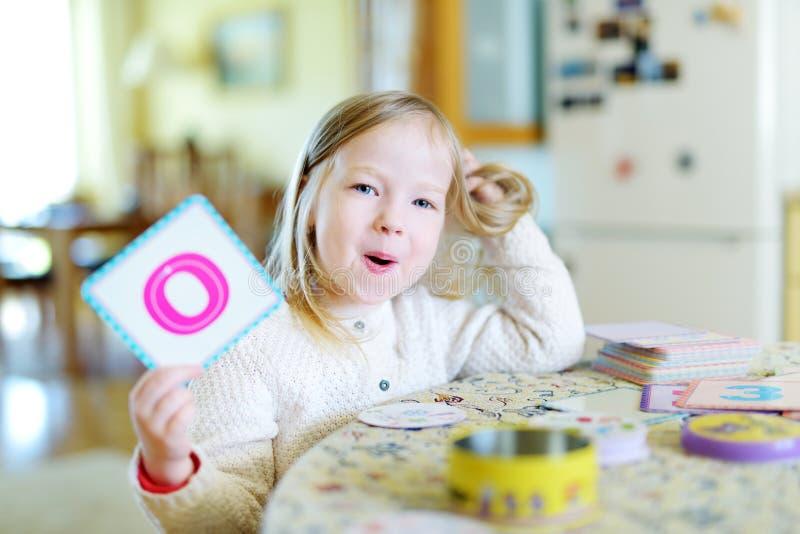 Funny little preschooler girl memorizing letters stock image