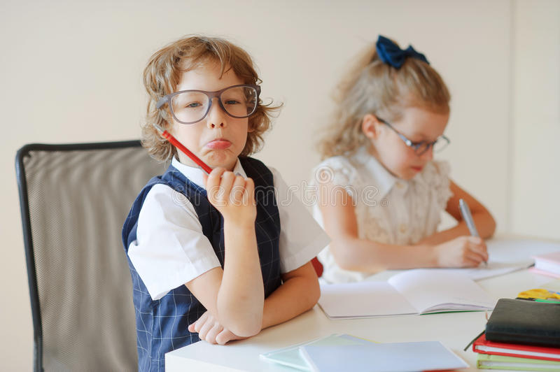 Funny little pupils sit at one desk. They are pupils of an elementary school. Boy fools around, girlie writes something with a serious look. On a school desk stock image