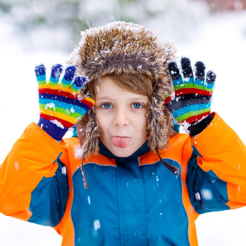 Funny little school kid boy in colorful clothes playing outdoors during snowfall. Active leisure with children in winter royalty free stock images