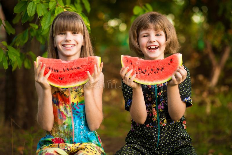 Funny little sisters girl eats watermelon in summer royalty free stock photos