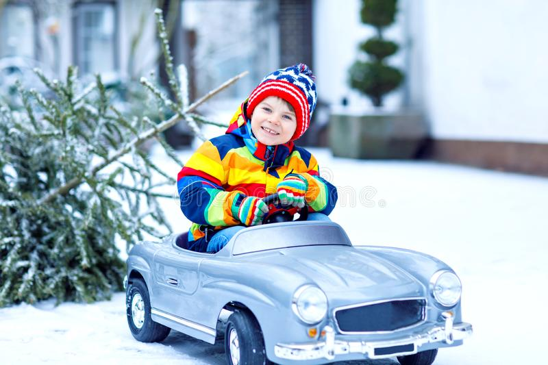 Funny little smiling kid boy driving toy car with Christmas tree. Happy child in winter fashion clothes bringing hewed stock photos