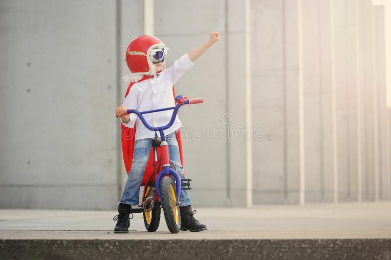 A funny, little superhero. Concept boy imagination. Happy childchood. A lovely, preschool child in a costume of supernatural hero. He is dressed in red cape stock image