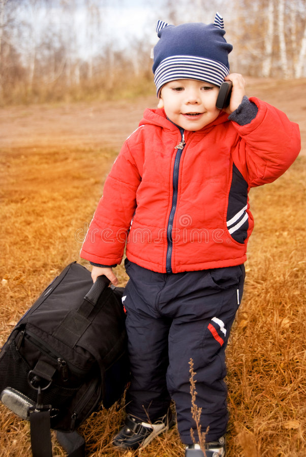 Funny little traveler with a bag and a cell-phone stock photography