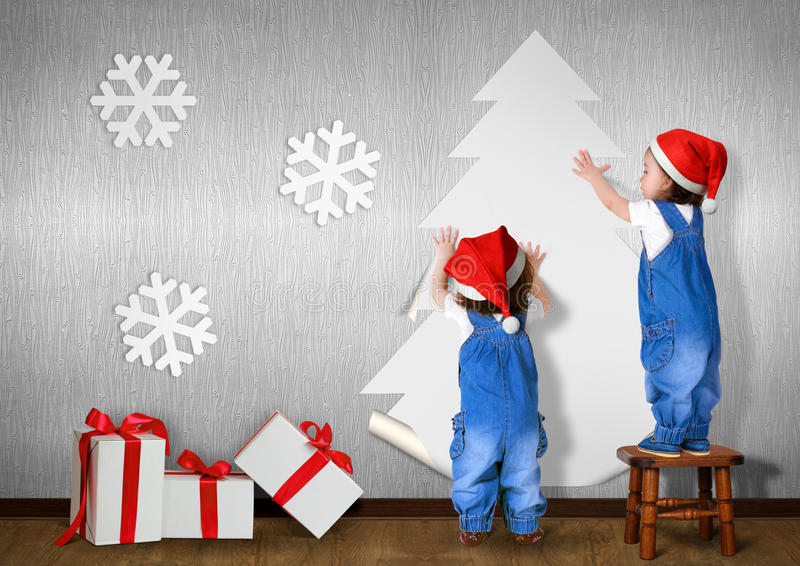 Funny Little twins dressed Santa hat, glue Christmas tree on wal stock photo