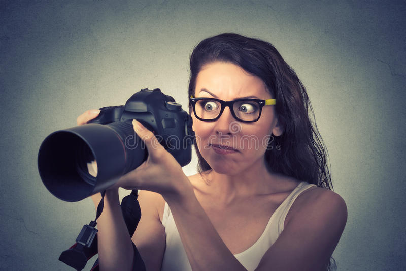 Funny looking young woman with digital camera royalty free stock images