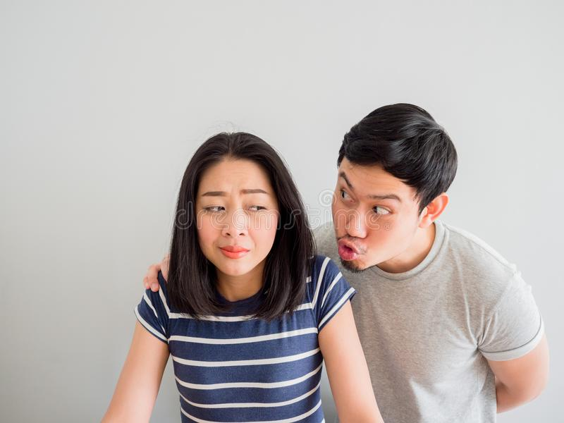 Funny lovely couple trying to kiss each other. Concept of comedy. Funny lovely Asian couple trying to kiss each other. Concept of comedy love stock photography