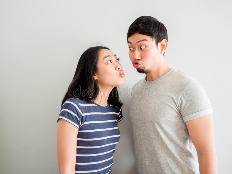 Funny lovely couple trying to kiss each other. Concept of comedy. Funny lovely Asian couple trying to kiss each other. Concept of comedy love stock images