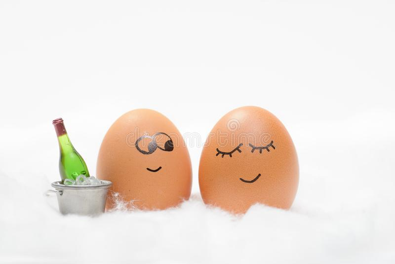 Funny lovely eggs in snow with bottle of wine stock images