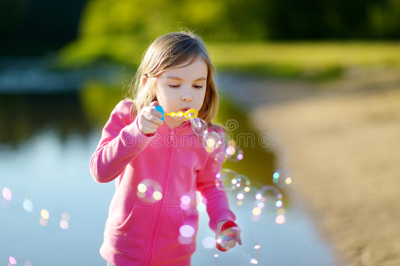 Funny lovely little girl blowing soap bubbles royalty free stock photo