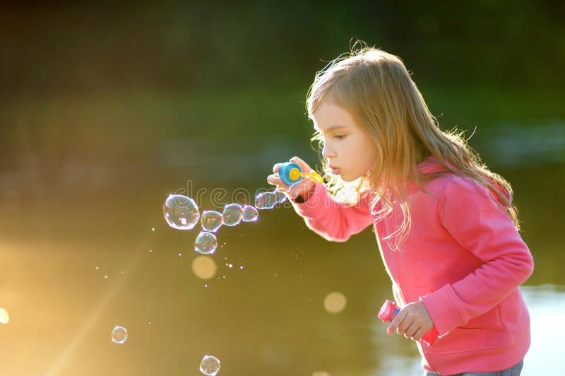 Funny lovely little girl blowing soap bubbles stock photos