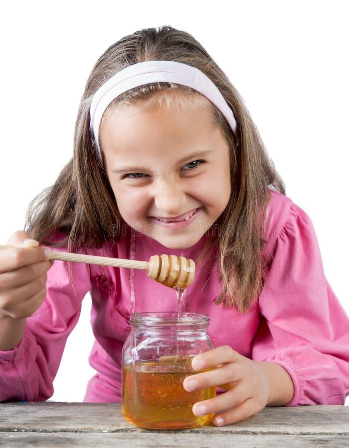 funny lovely little girl eat honey stock photography