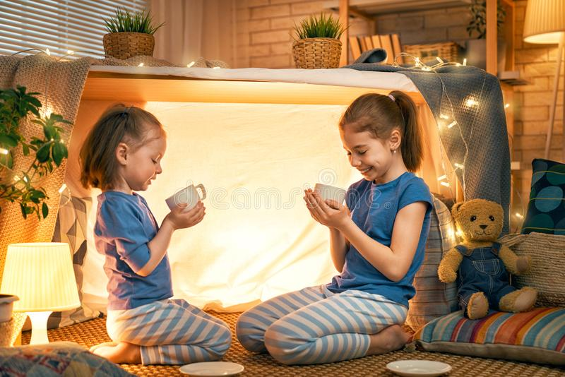 Funny lovely sisters. Two cute happy girls play at home. Funny lovely sisters are having fun in children room. Girls play tea-party and drink tea from cups stock image