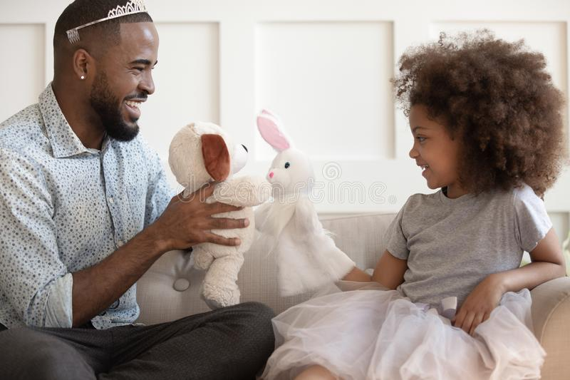 Funny biracial dad have fun playing with little daughter stock images