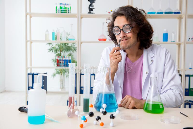 Funny male chemist working in the lab royalty free stock image
