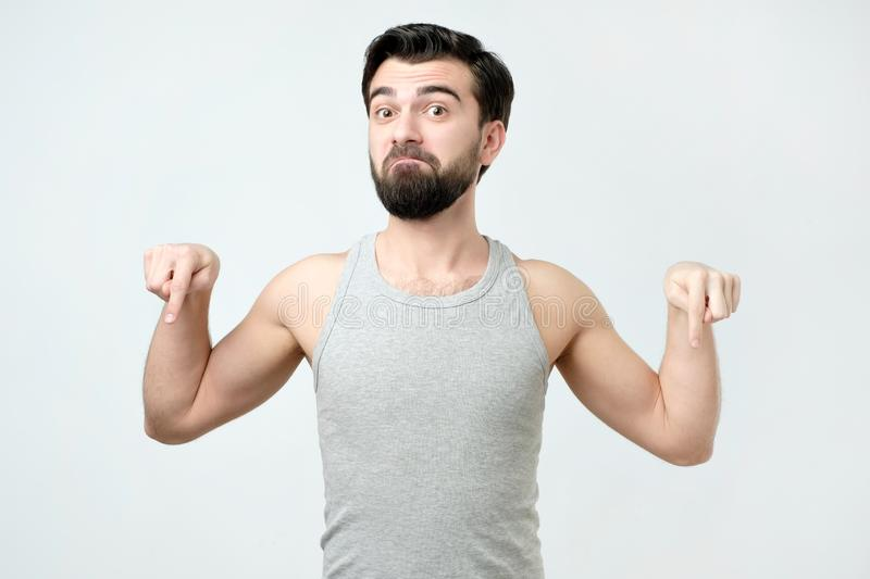 Funny male looks and pointing down as shows something, sees comic things royalty free stock photo