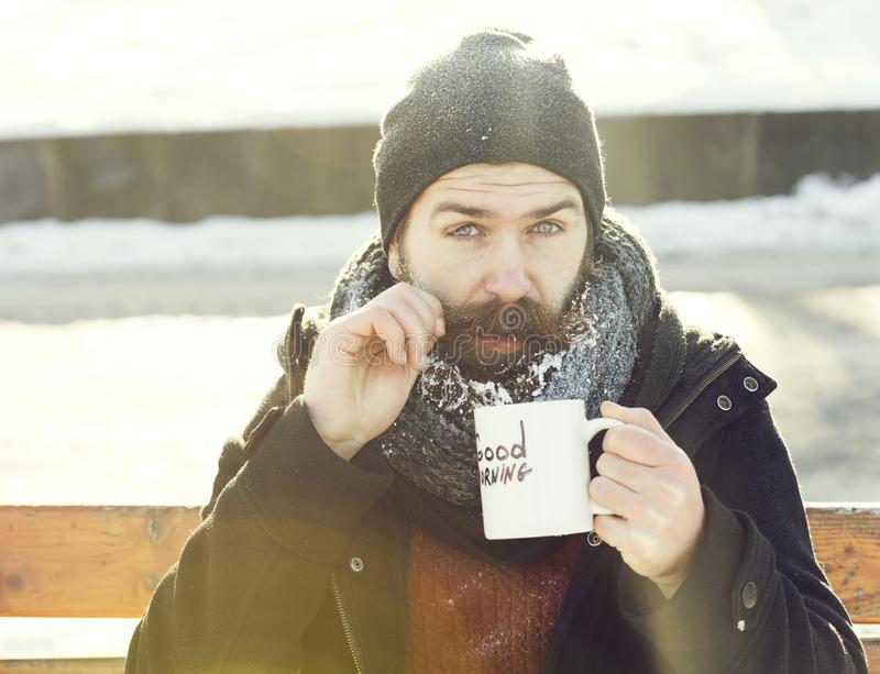 Funny man, bearded hipster with beard and moustache covered with white frost drinks from cup with good morning text. Sitting on wooden bench on snowy winter day stock photo