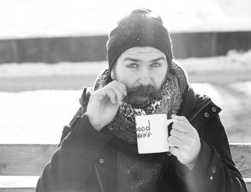 Funny man, bearded hipster with beard and moustache covered with white frost drinks from cup with good morning text. Sitting on wooden bench on snowy winter day stock photos