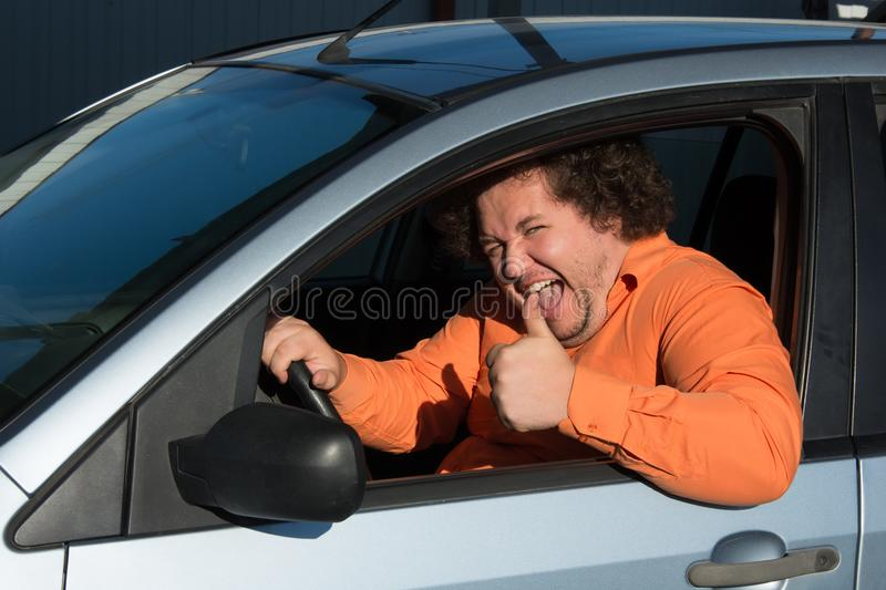 Funny fat man in the car. Funny man in the car. Road problems and difficulties in the way stock photography