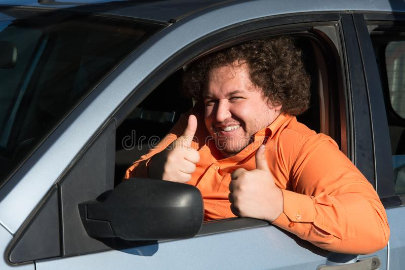 Funny fat man in the car. Funny man in the car. Road problems and difficulties in the way stock image